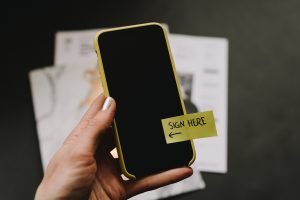 smart phone with sign here sticky note